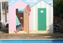 Trompe l'oeil beach huts painted looking onto an outdoor swimming pool in London