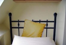 Trompe l'oeil of iron bedheads and cushions for a B&B